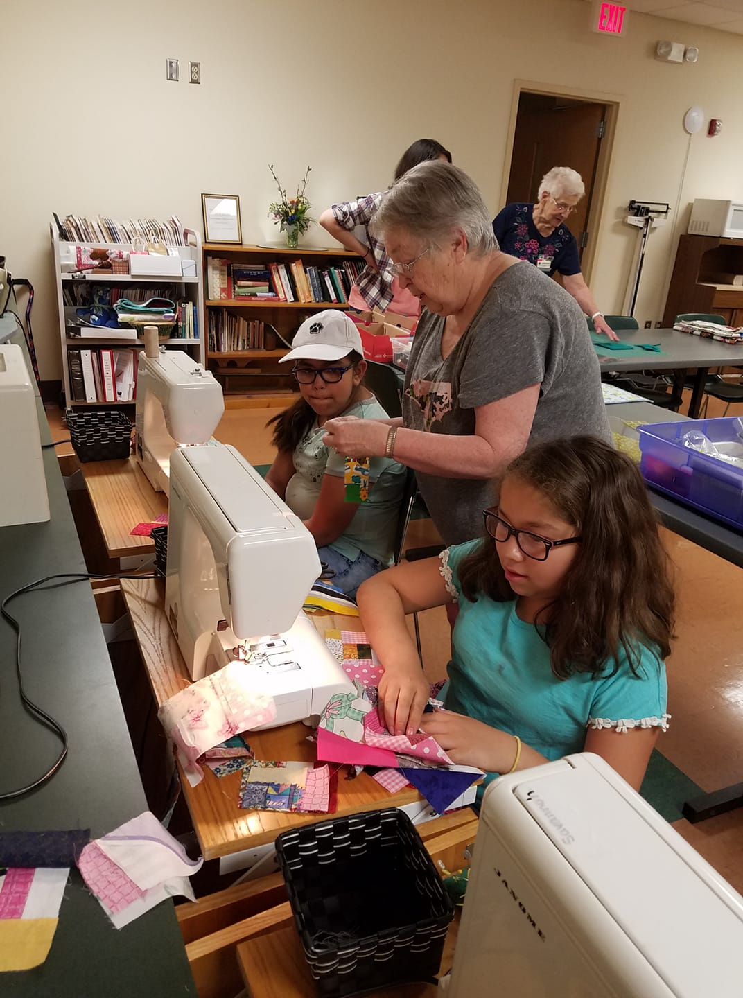 adult quilters helping youth participants sew quilt blocks