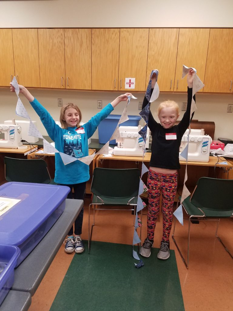 Young 4-Hers holding up sewing project